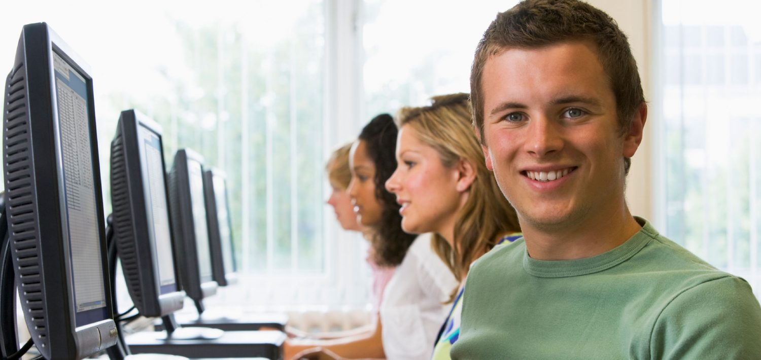 Business student seated at a computer smiling.