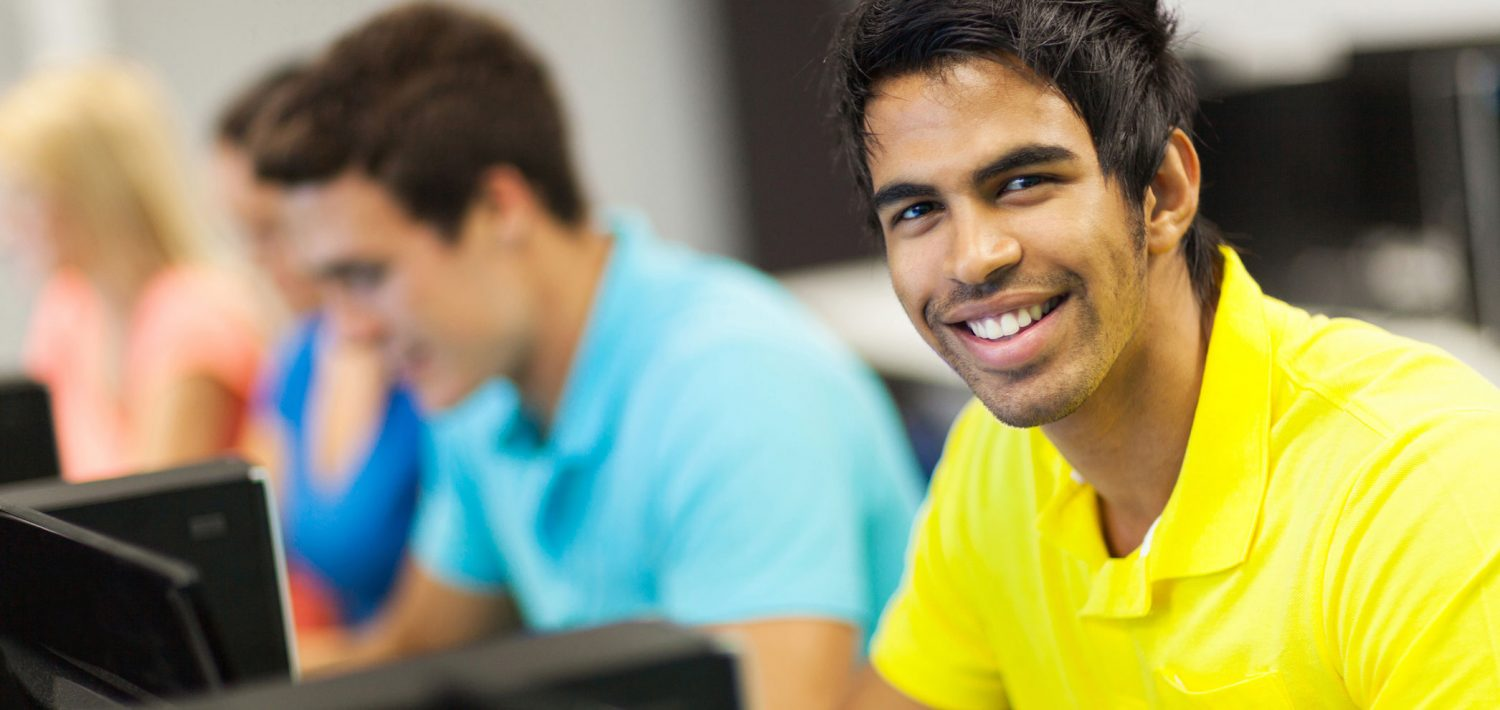 Male student smiling as he works on a project in class.