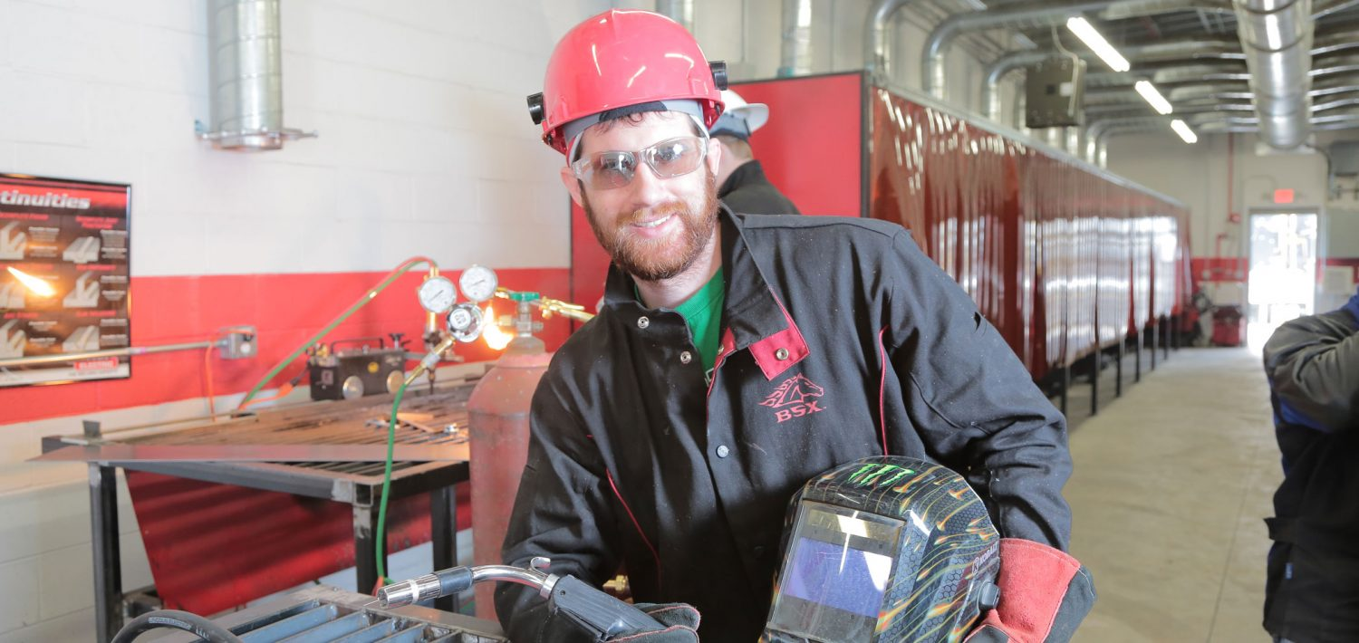 Welding student standing and holding his equipment.